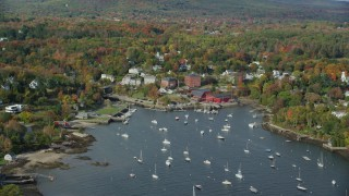 AX148_100 - 6k stock footage aerial video orbiting small coastal town, Rockport Harbor, autumn, Rockport, Maine