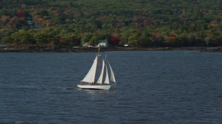 AX148_105 - 6k stock footage aerial video orbiting a sailboat, West Penobscot Bay, autumn, Rockport, Maine