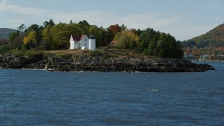 AX148_109 - 6k stock footage aerial video approaching Curtis Island Light, reveal small coastal town, autumn, Camden, Maine
