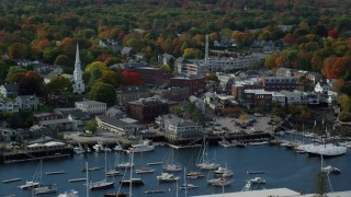 AX148_112 - 6k stock footage aerial video flying by small coastal town near harbor, autumn, Camden, Maine