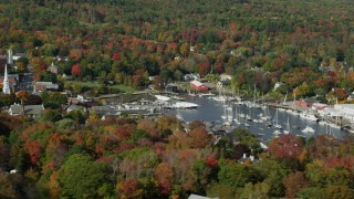AX148_120 - 6k stock footage aerial video flying by small coastal town and Camden Harbor, autumn, Camden, Maine