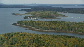 AX148_124 - 6k stock footage aerial video flying by Grindel Point Light, ferry, Isleboro Island, autumn, Islesboro, Maine