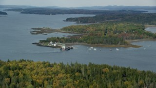 AX148_125 - 6k stock footage aerial video flying by Grindel Point Light, islands, ferry, tilt down, autumn, Islesboro, Maine