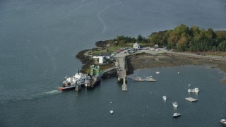 AX148_126 - 6k stock footage aerial video flying by Grindel Point Light, ferry, islands, autumn, Islesboro, Maine