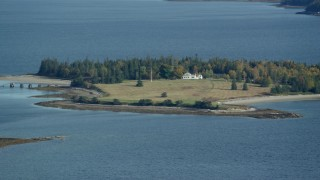 AX148_131 - 6k stock footage aerial video flying by an isolated island home, trees in autumn, Hog Island, Maine
