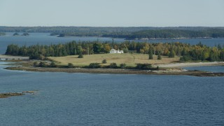 AX148_133 - 6k stock footage aerial video approaching an isolated island home in autumn, Hog Island, Maine