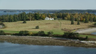 AX148_134 - 6k stock footage aerial video approaching an isolated island home in autumn, Hog Island, Maine