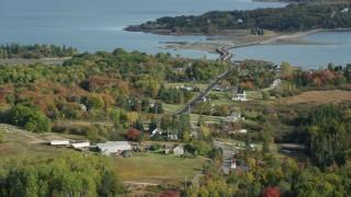 AX148_138 - 6k stock footage aerial video flying by island homes, Little Deer Isle Road, autumn, Little Deer Isle, Maine