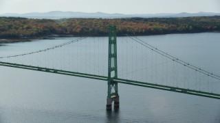 AX148_141 - 6k stock footage aerial video orbiting the Deer Isle Bridge, dense trees, autumn, Deer Isle Bridge, Maine