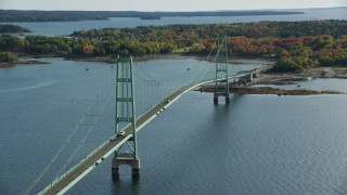 AX148_142 - 6k stock footage aerial video orbiting the Deer Isle Bridge, colorful trees in autumn, Little Deer Isle, Maine