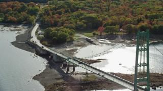 AX148_144 - 6k stock footage aerial video tracking cars on Deer Isle Bridge, Deer Isle Road, autumn, Little Deer Isle, Maine
