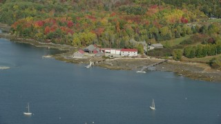 AX148_148 - 6k stock footage aerial video flying by boat dealer dock and garage, forest, autumn, Brooklin, Maine