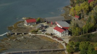 AX148_149 - 6k stock footage aerial video flying by a boat dealer dock and garage, autumn, Brooklin, Maine
