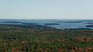 AX148_150 - 6k stock footage aerial video flying by colorful forest, small islands in the bay, autumn, Brooklin, Maine