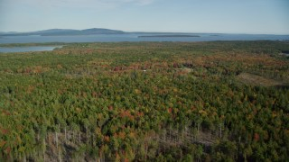 AX148_151 - 6k stock footage aerial video flying over colorful forest in autumn, Brooklin, Maine