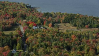 AX148_152 - 6k stock footage aerial video flying by rural home, colorful forest in autumn, Brooklin, Maine