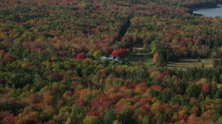 AX148_153 - 6k stock footage aerial video flying by an isolated home, colorful forest near shore, autumn, Brooklin, Maine