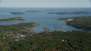 AX148_159 - 6k stock footage aerial video flying over trees in autumn, approaching the Southwest Harbor, Maine