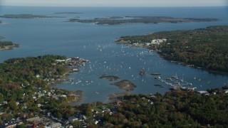 AX148_160 - 6K stock footage aerial video flying by small coastal town, autumn, Southwest Harbor, Mount Desert Island, Maine