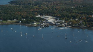 AX148_162 - 6K stock footage aerial video flying by waterfront warehouse buildings, autumn, Southwest Harbor, Maine