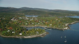 AX148_163 - 6K stock footage aerial video flying by small coastal town in autumn, Northeast Harbor, Mount Desert Island, Maine
