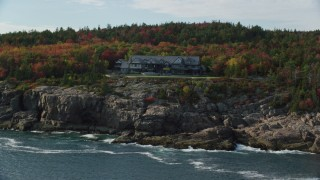 AX148_173 - 6K stock footage aerial video approaching an isolated waterfront mansion, autumn, Seal Harbor, Maine
