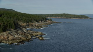 AX148_175 - 6K stock footage aerial video flying by a forested coastline, Seal Harbor, Mount Desert Island, Maine