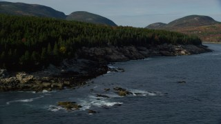 AX148_176 - 6K stock footage aerial video flying by a rocky, forest coastline, Seal Harbor, Mount Desert Island, Maine