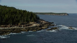 AX148_177 - 6K stock footage aerial video flying by forested, rocky coastline, autumn, Seal Harbor, Mount Desert Island, Maine