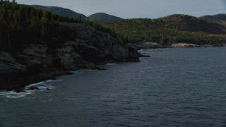 AX148_178 - 6K stock footage aerial video flying by a rocky, forested coastline, autumn, Seal Harbor, Maine