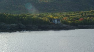 AX148_183 - 6K stock footage aerial video approaching waterfront mansion, autumn, Bar Harbor, Maine
