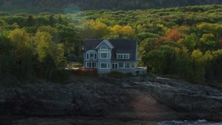AX148_184 - 6K stock footage aerial video approaching waterfront mansion, autumn, Bar Harbor, Maine