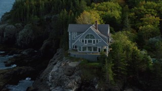 AX148_185 - 6K stock footage aerial video flying away from waterfront mansion, revealing coast, autumn, Bar Harbor, Maine