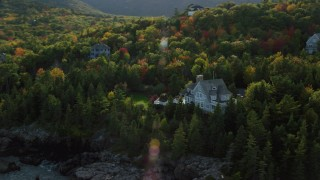 AX148_190 - 6K stock footage aerial video flying by waterfront mansion, rocky coat, autumn, Bar Harbor, Maine