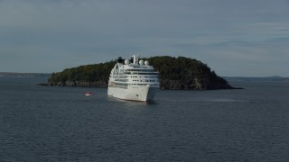 AX148_194 - 6K stock footage aerial video flying by a cruise ship, tiny island, Bar Harbor, Maine