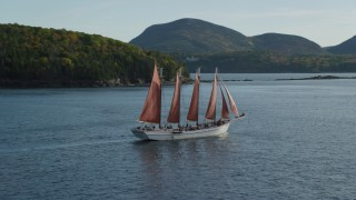 AX148_198 - 6K stock footage aerial video sailing ship and partial fall foliage, Bar Harbor, Maine