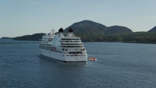 AX148_200 - 6K stock footage aerial video tracking a cruise ship set against a tiny island, Bar Harbor, Maine