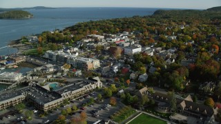 AX148_202 - 6K stock footage aerial video orbiting Harborside Hotel, Spa & Marina in coastal town, autumn, Bar Harbor, Maine
