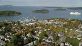 AX148_204 - 6K stock footage aerial video flying away from harbor and over coastal town with fall foliage, Bar Harbor, Maine