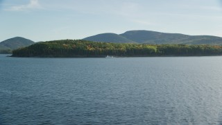 AX148_209 - 6K stock footage aerial video flying over water toward ferry and island with fall foliage, Bar Harbor, Maine