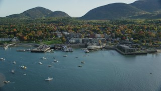 AX148_212 - 6K stock footage aerial video flying over harbor toward small coastal town and fall foliage, autumn, Bar Harbor, Maine