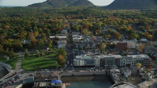 AX148_213 - 6K stock footage aerial video flying over docked ferries toward Main Street in coastal town with fall foliage, Bar Harbor, Maine