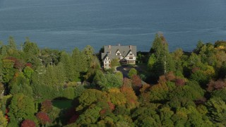 AX148_215 - 6K stock footage aerial video flying by isolated waterfront home and fall foliage, Bar Harbor, Maine
