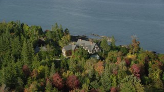 AX148_216 - 6K stock footage aerial video orbiting isolated waterfront home among partial fall foliage, Bar Harbor, Maine