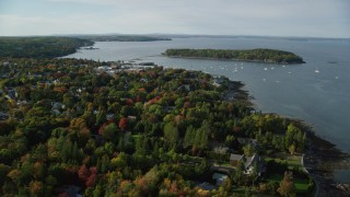 AX148_217 - 6K stock footage aerial video flying over fall foliage in a small coastal town toward harbor, autumn, Bar Harbor, Maine