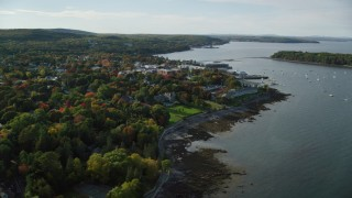 AX148_218 - 6K stock footage aerial video flying by coastal town with fall foliage and over the harbor, Bar Harbor, Maine