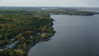 AX148_224 - 6K stock footage aerial video flying over water toward rode winding through forest with partial fall foliage, Bar Harbor, Maine
