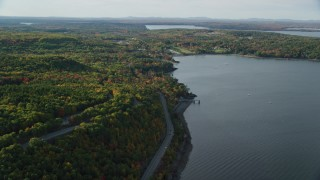 AX148_225 - 6K stock footage aerial video flying over water and forest with fall foliage, Bar Harbor, Maine