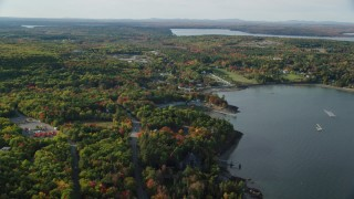 AX148_226 - 6K stock footage aerial video flying over forest of partial fall foliage toward a coastal town, Bar Harbor, Maine