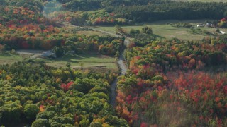 AX148_228 - 6K stock footage aerial video following a road through the countryside with fall foliage, Bar Harbor, Maine